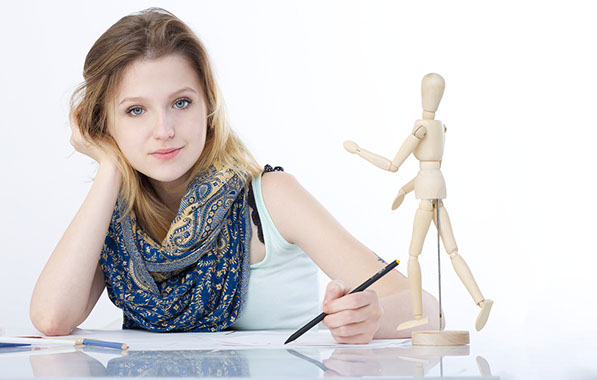 Young art director working at a table with her artist's mannequin