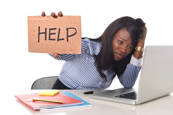 "Businesswoman working on a computer and holding up a ""Help"" sign."